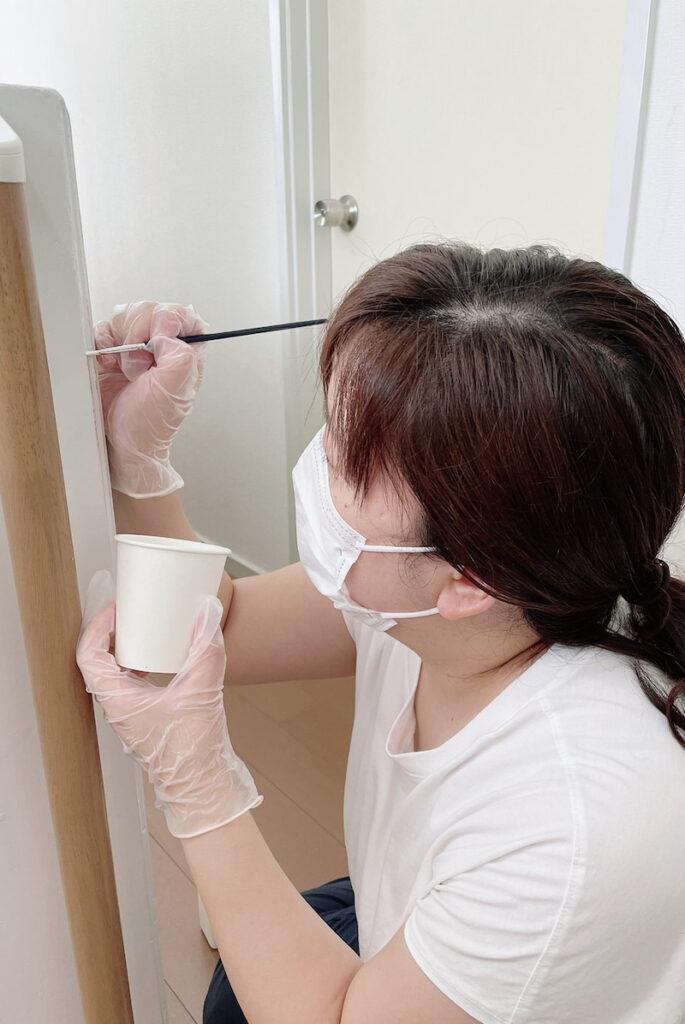白い塗料を塗っている女性
