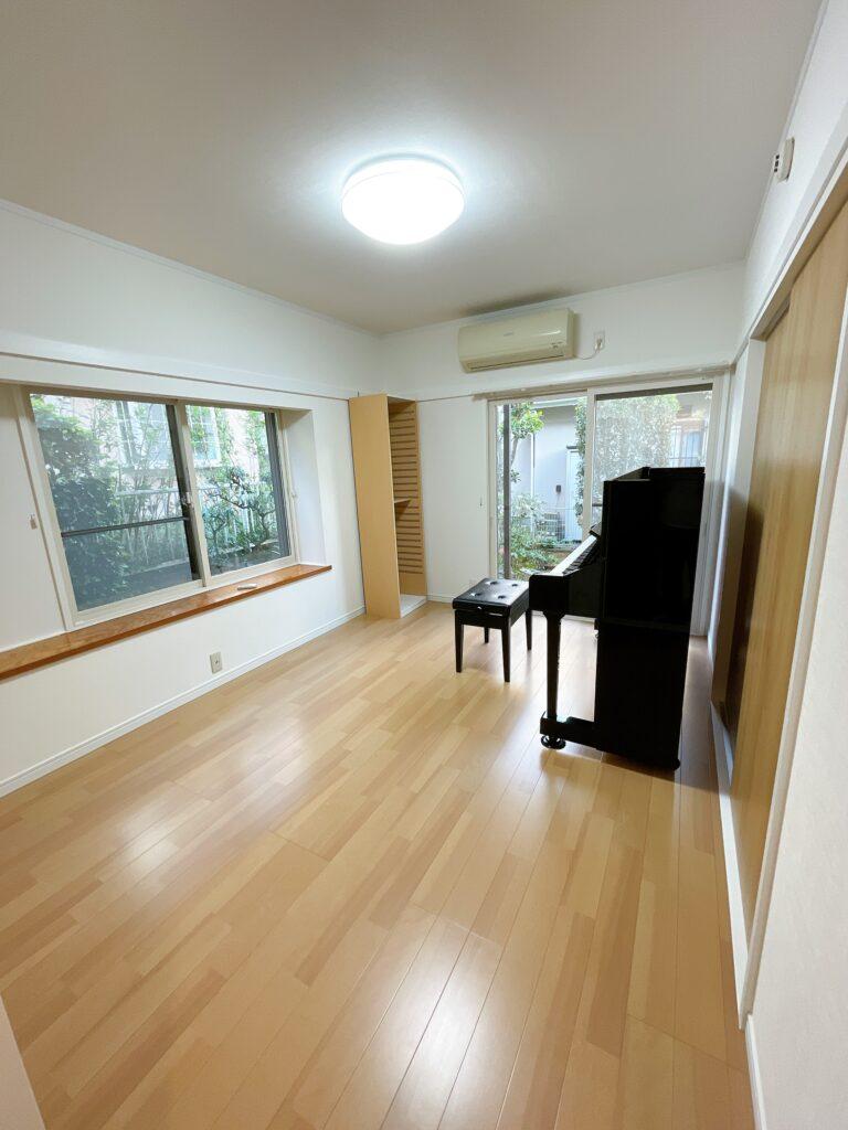 黒いアップライトピアノがある部屋