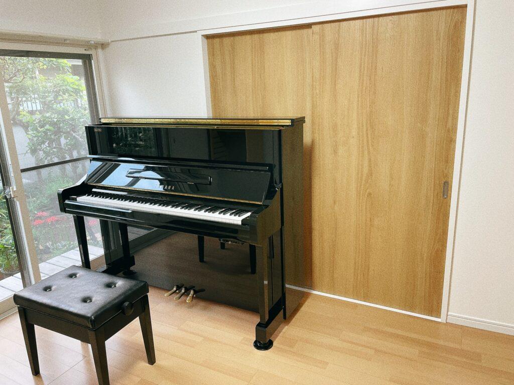 黒いアップライトピアノと北欧風の部屋
