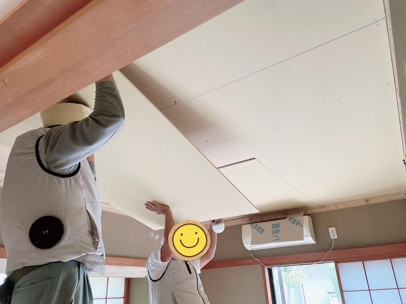 大工さんが2人で天井の板を上げている